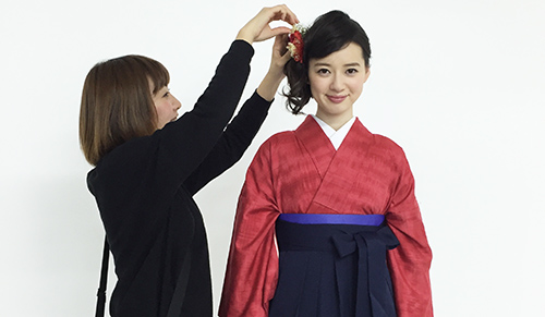 撮影中に髪飾りを調整するヘアメイク